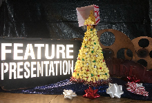 christmas tree on purple fabric with feature presentation sign in background