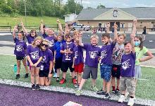 Kids on football field wearing purple cheering