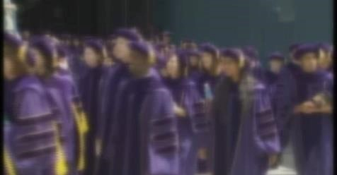 Students wearing purple cap and gowns during graduatin ceremony