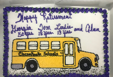 cake with white, purple icing with a yellow school bus that reads congratulations