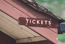 old wood building with tickets sign