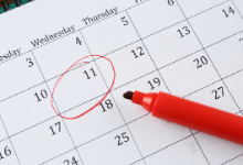 Picture of monthly calendar with a red highlighter laying in the middle of it. Also, their is a red highlight circled around the 11th day of the month