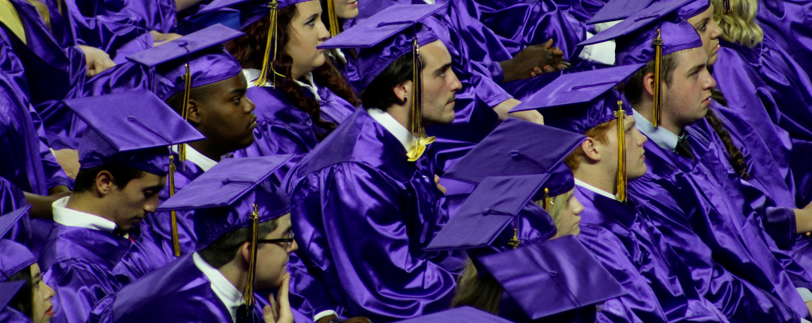 Purple graduation cap and gown group picture