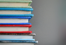 green, blue, purple, red, black books stacked with a grey background.