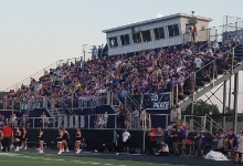 A photo of the chesapeake local school district football field bleachers loaded up with chesapeake football fans, mostly wearing purple.
