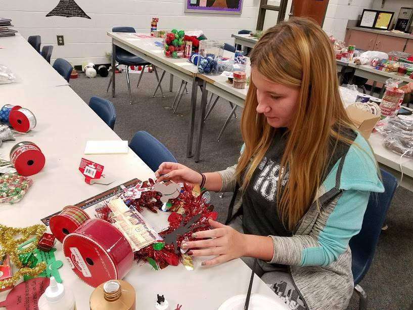 Hannah King making teacher wreaths for Christmas.