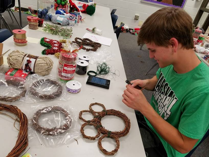 Andrew Mayenschein making teacher wreaths for Christmas.