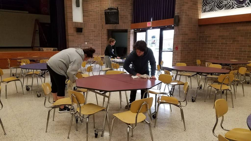 Josie Garrido, Selena Bragg, and Tyler Eddy join in cleaning the cafeteria during PEAKE.