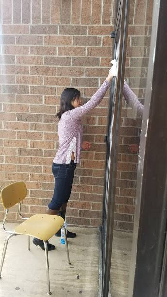 Haley Mays cleaning glass throughout the school.