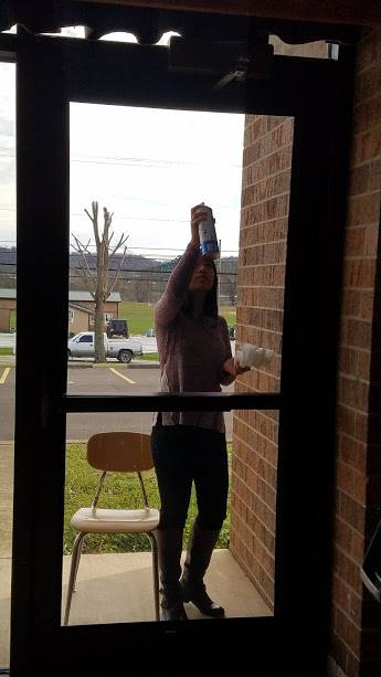 Haley Mays cleans windows throughout the school as part of the PEAKE community service class.