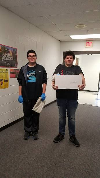 Brennan Smith and Evan Goodall clean desks throughout the school during PEAKE.