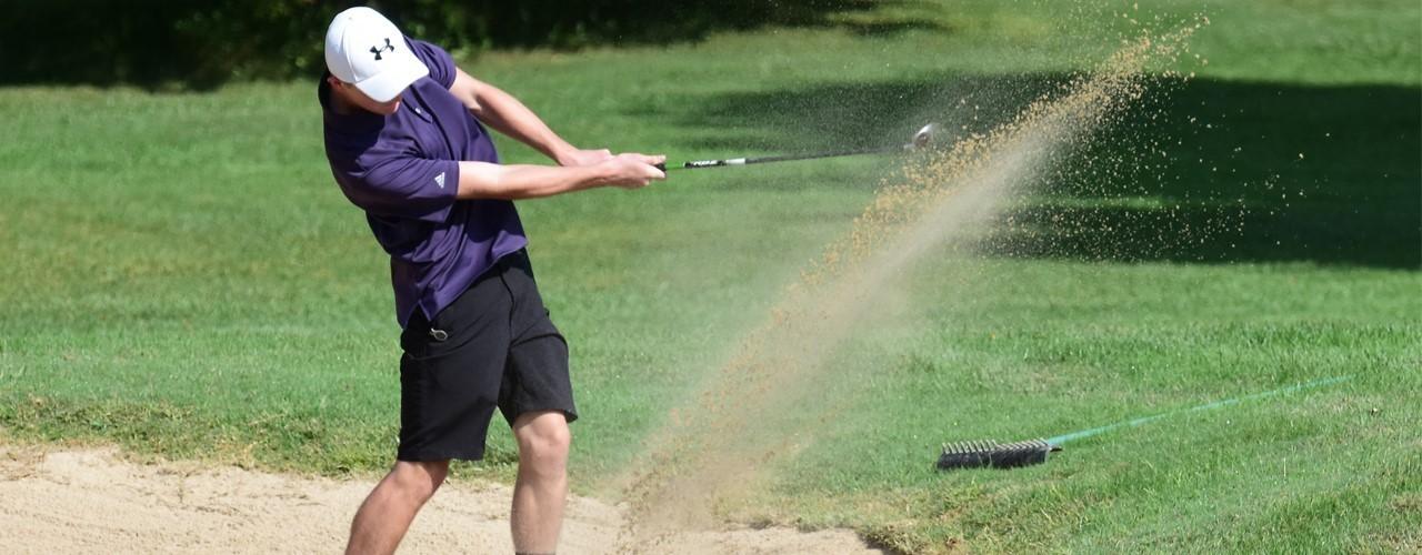 Golfer swinging club in sand trap