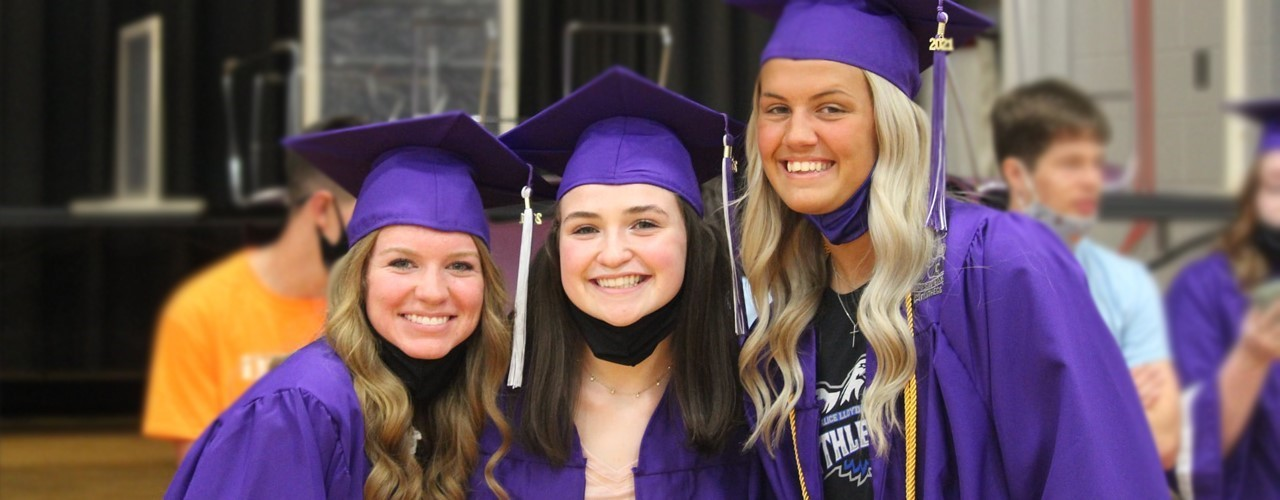 Purple Cap and Gown with three girls smiling