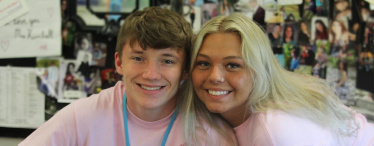 guy girl wearing pink shirts smiling
