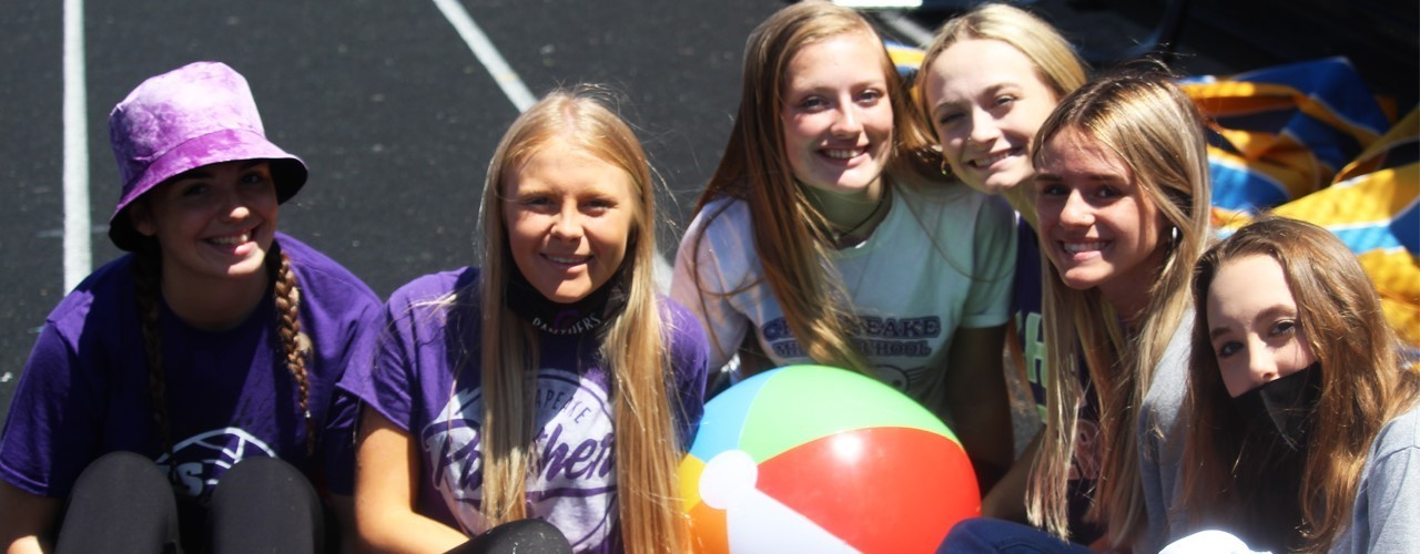 6 girls during senior even smiling sitting on running track