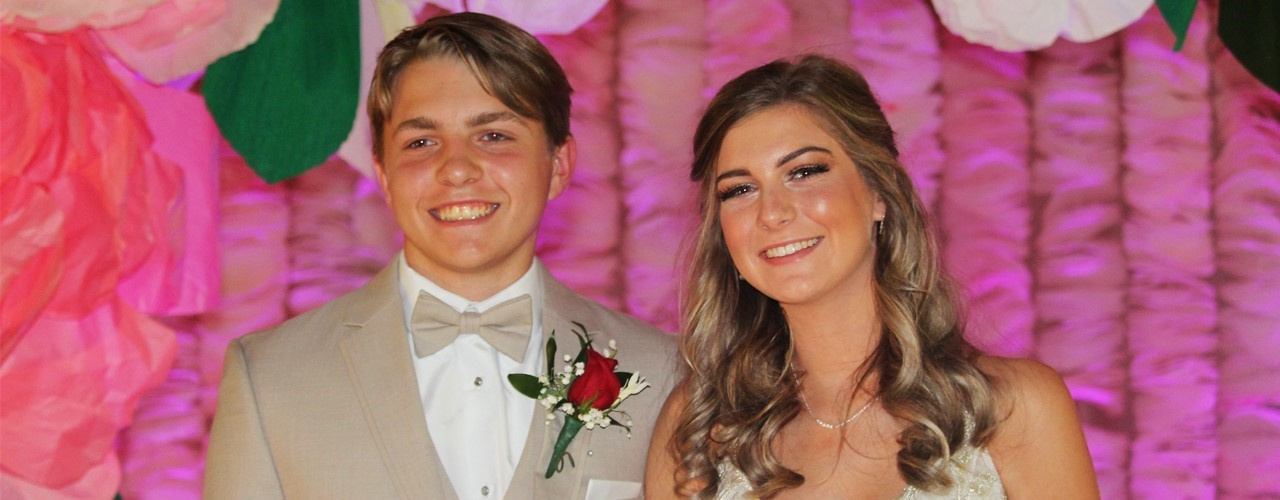 guy and girl in tuxedo and prom dress in front of pink background