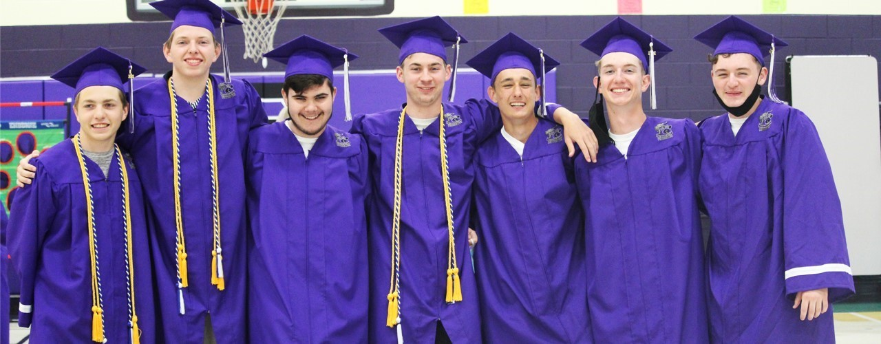 graduates wearing purple cap and gown