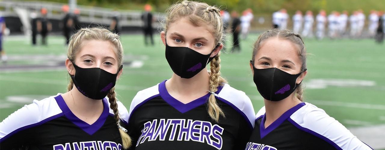 Cheerleaders standing on field wearing masks