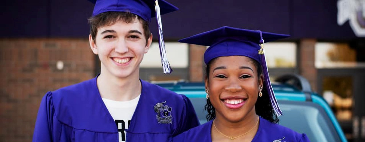 2 graduates wearing purple cap and gown.