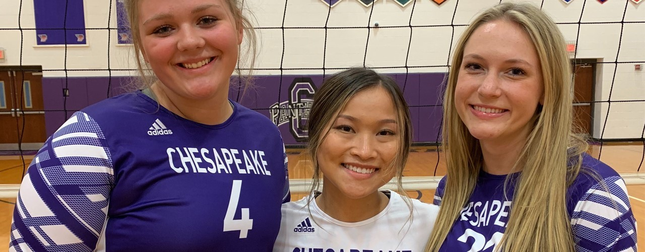 3 volleyball girls wearing purple in front of net